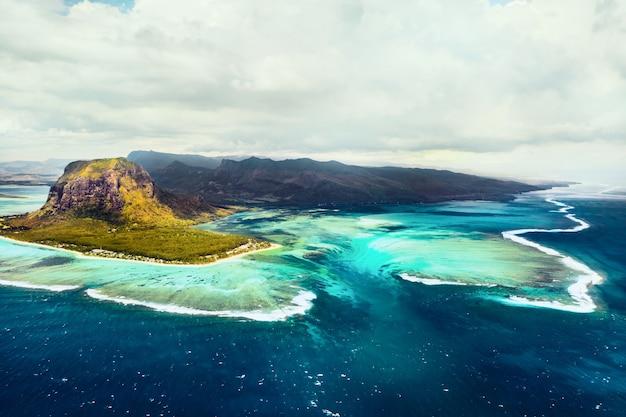 Вид с высоты птичьего полета на ле морн брабант, объект всемирного наследия юнеско. коралловый риф острова маврикий. грозовое облако.