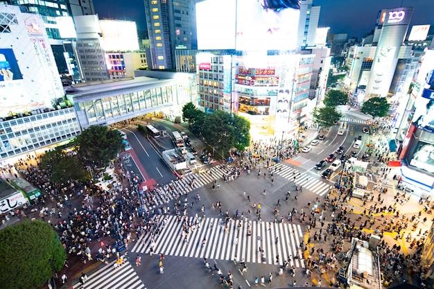 Вид с высоты птичьего полета на толпу, пересекающую пересеченную перекресток в сибуя (токио, япония)