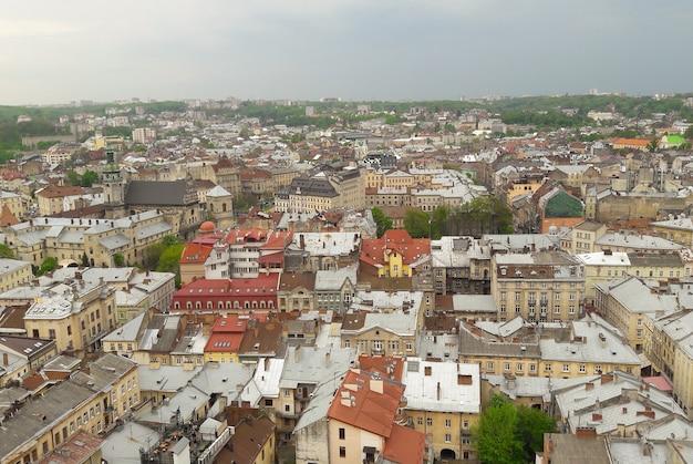 갈색 기와 지붕이 있는 중세 도시의 조감도. 구름이 있는 푸른 하늘을 배경으로