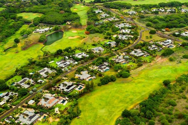 Вид с высоты птичьего полета на город и поля для гольфа на острове маврикий. виллы на острове маврикий. поле для гольфа.