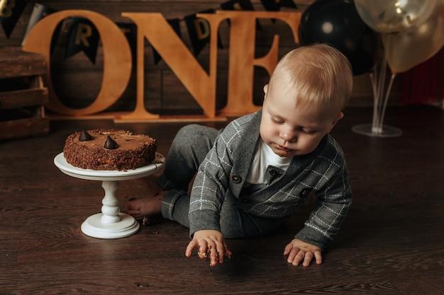 Именинник в сером костюме ест шоколадный торт на коричневом фоне