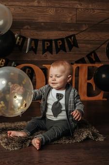 Именинник в сером костюме сидит и играет с воздушным шариком на коричневом фоне