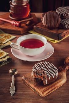 木製のテーブルに磁器のお茶、ミツバチ、シナモンで覆われた、かまれたブラジルのハニークッキーチョコレート-pao de mel