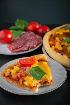 Кусок пиццы на черной поверхности. надкушенный кусок вкусной итальянской пиццы
