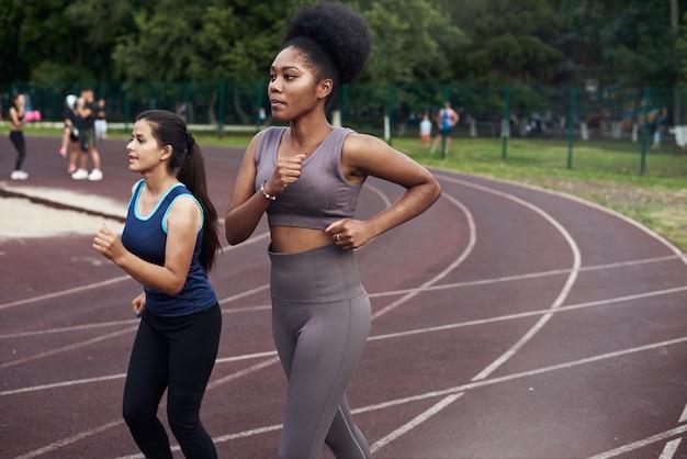 Черно-кавказская девушка бегает по улице в специализированном месте. спорт - это жизнь