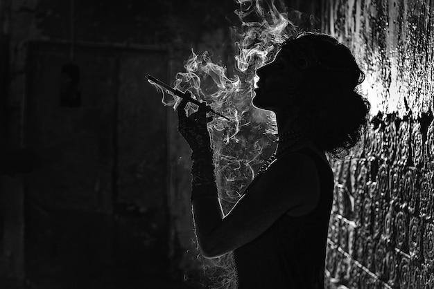 Черно-белый силуэт портрет молодой женщины, курящей сигарету в мундштуке.