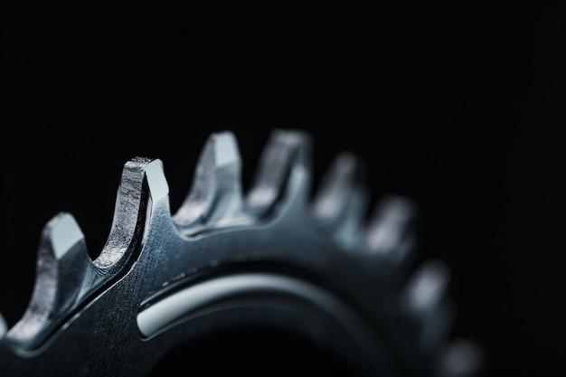 暗い背景に対照的な繰り返し歯車を持つ黒い自転車の運転星