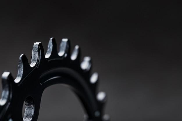 暗い表面に対照的な繰り返し歯車を備えた黒い自転車の運転星