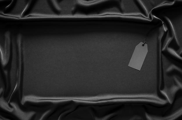 テキスト用のスペースがある黒い滑らかで波状の布に黒い空白の値札。ブラックフライデーのコンセプト。