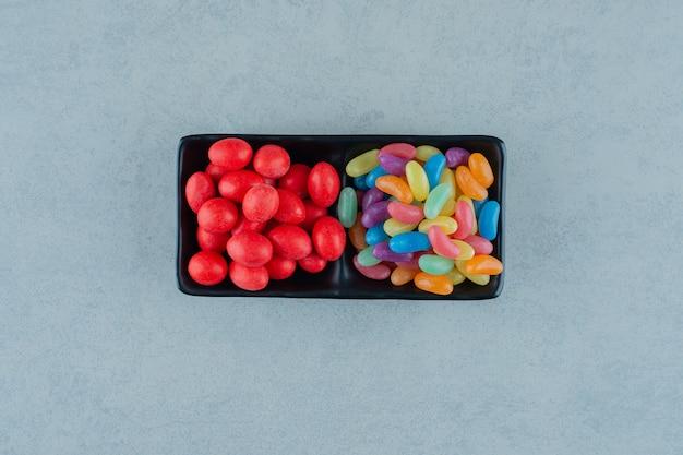 흰색 표면에 다채로운 콩 사탕으로 가득한 블랙 보드