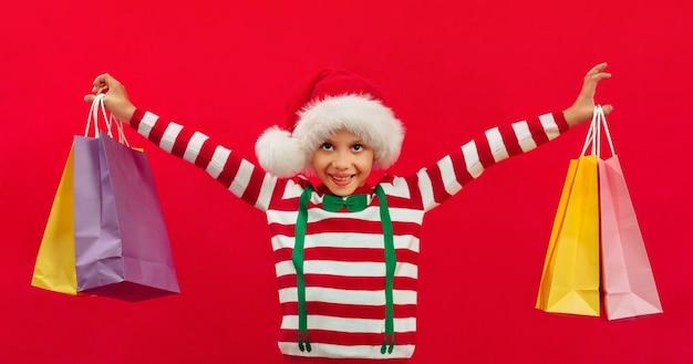 サンタの帽子をかぶって、キャリーバッグを持った黒人の少年が手に贈り物を持っていますクリスマスの買い物