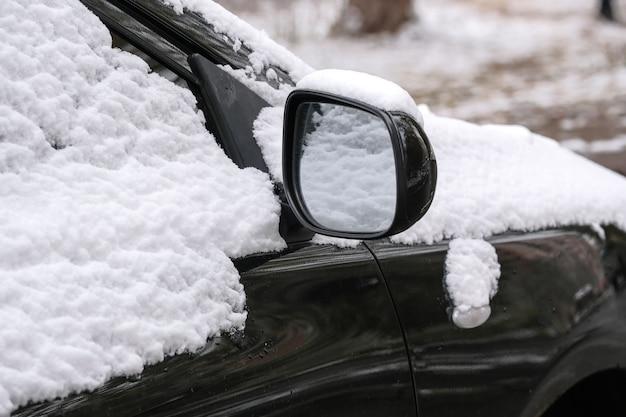 Черная машина припаркована возле жилого дома в городе, покрытого первым осенним снегом. фрагмент крупным планом.