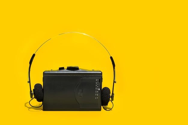 黄色の背景に黒いカセットプレーヤー