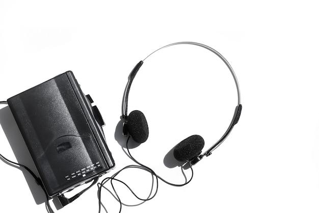 白い背景の上のヘッドフォンと黒いカセットプレーヤー