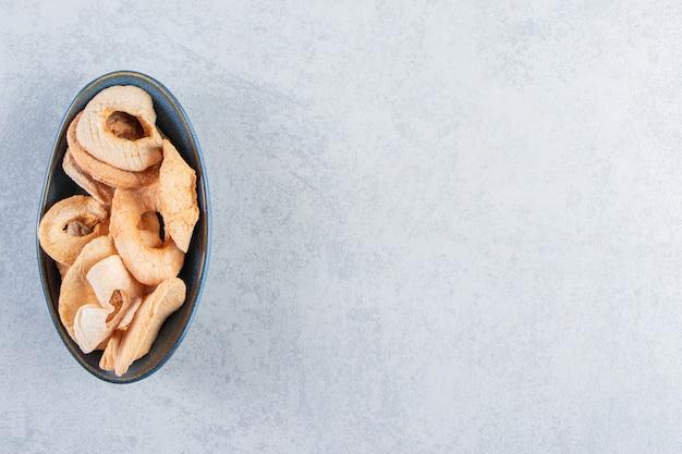 Черная глубокая тарелка со здоровыми сушеными яблоками на каменном фоне.