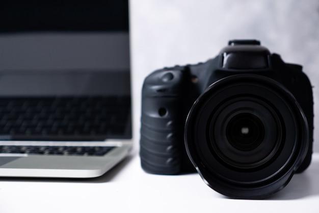 テーブルの上の黒いデジタルカメラとコンピューターのラップトップ。