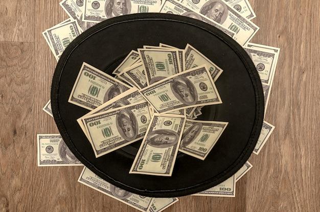 На полу лежит черная фетровая шляпа с деньгами. винтажная ретро шляпа. вид сверху.