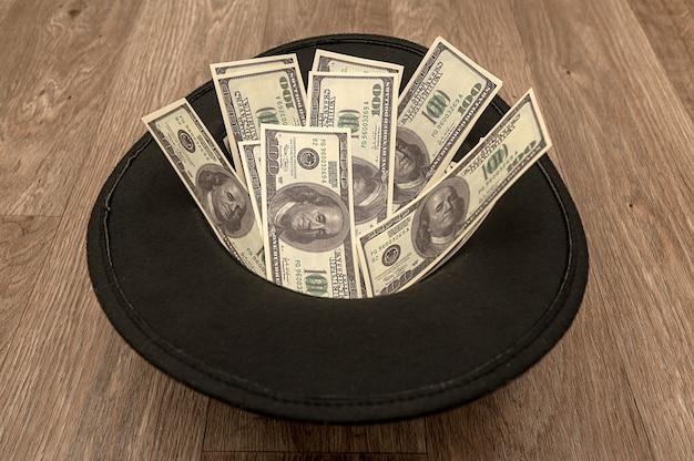 На полу лежит черная фетровая шляпа с деньгами. винтажная ретро шляпа.