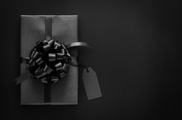 Черная подарочная коробка с лентой и пустым ценником кладет на черный фон. черная пятница и концепция дня подарков.