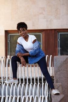 Черная девушка сидит на ступеньках города. равенство