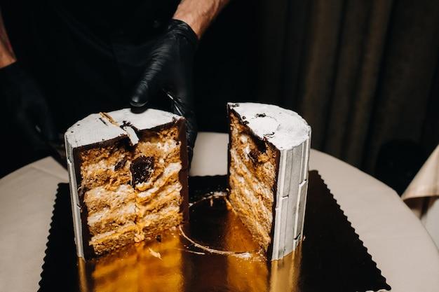 黒手袋をしたシェフがチョコレートのウエディングケーキをスライスしています
