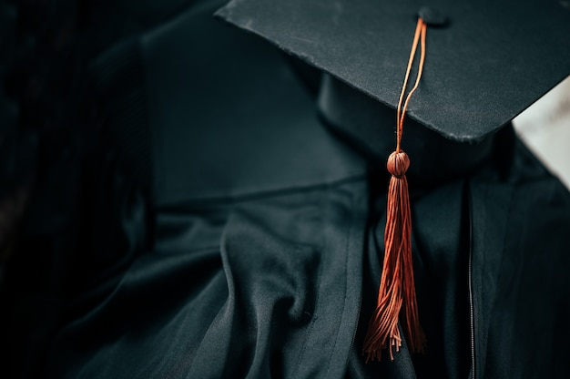 卒業式のガウンには、茶色のタッセルが付いた黒い卒業帽が置かれています。