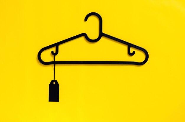 黄色の背景に空白の黒い値札が付いた黒いハンガー。ブラックフライデーのコンセプト。