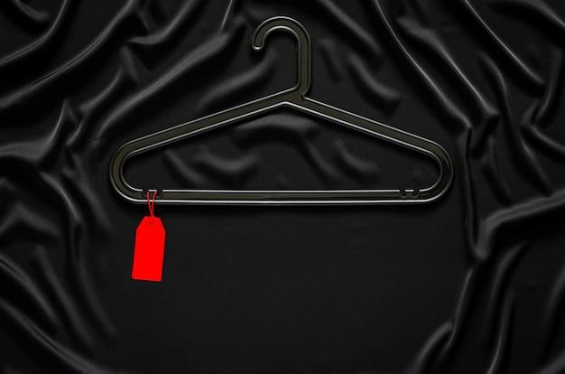 テキスト用のスペースのある黒い滑らかで波状の布に空白の赤い値札が付いた黒いハンガー。ブラックフライデーのコンセプト。
