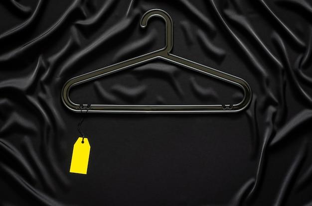 テキスト用のスペースのある黒い滑らかで波状の布に空白の黄色の値札が付いた黒いハンガー。ブラックフライデーのコンセプト。