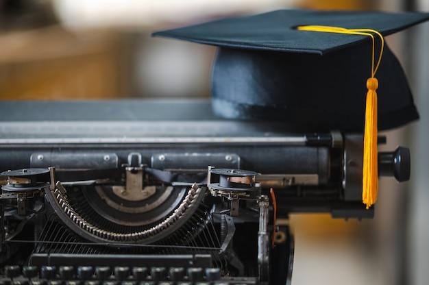 タイプライターに卒業生の黄色いタッセルが付いた黒い帽子をかぶる。