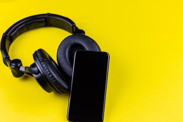 黄色いテーブルの上の黒いヘッドフォンと携帯電話。あらゆるものを通して音楽を聴く、音楽ワイヤレスストリーミングの概念。
