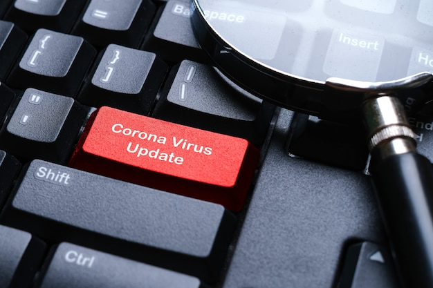 Covid-19 전염병 바이러스 발생의 현재 상황에 따라 코로나바이러스 업데이트로 작성된 빨간색 버튼이 있는 검은색 키보드.