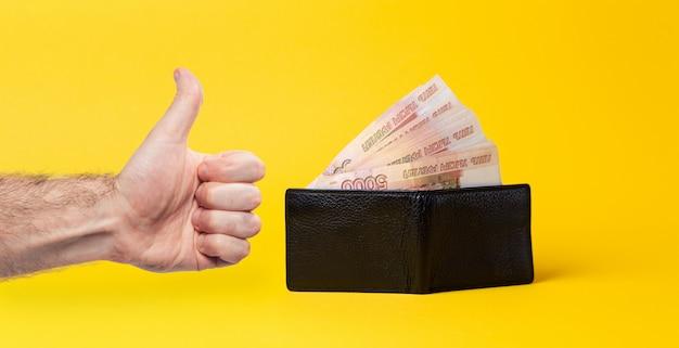 Открылся черный кожаный кошелек, набитый веером на пять тысяч рублей. рука мужчины показывает палец вверх. желтый фон. концепция экономического процветания.