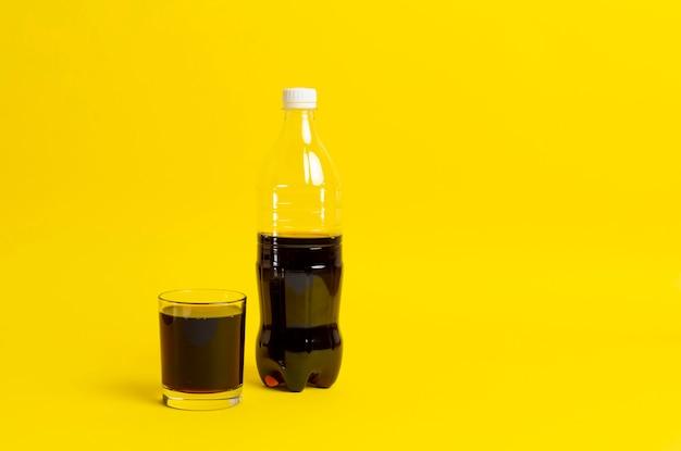 ガラスに注がれた黒いレモネード、色の背景に分離されたソーダのボトル