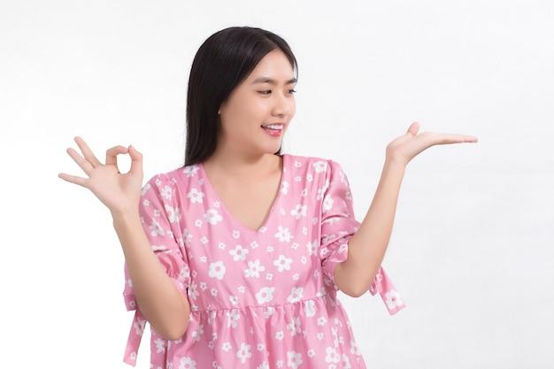 핑크 드레스를 입고 검은 장발 아시아 귀여운 여자가 그녀의 손을보고있다