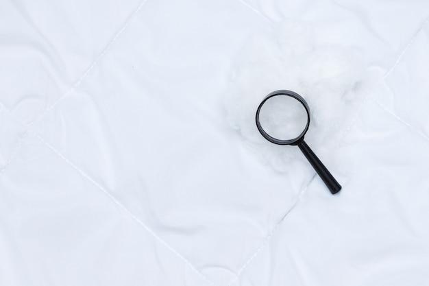 黒い毛布の上に黒い拡大鏡があります。寝室のナンキンムシを検出する。