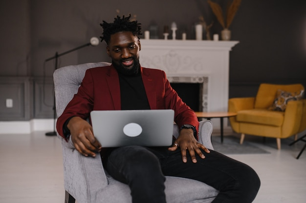 Черный мужчина работает на ноутбуке крупным планом во время видеоконференций