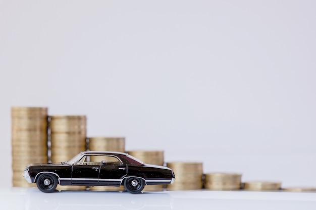 白い背景の上のヒストグラムの形でコインが付いている車の黒いモデル。融資、貯蓄、保険の概念。
