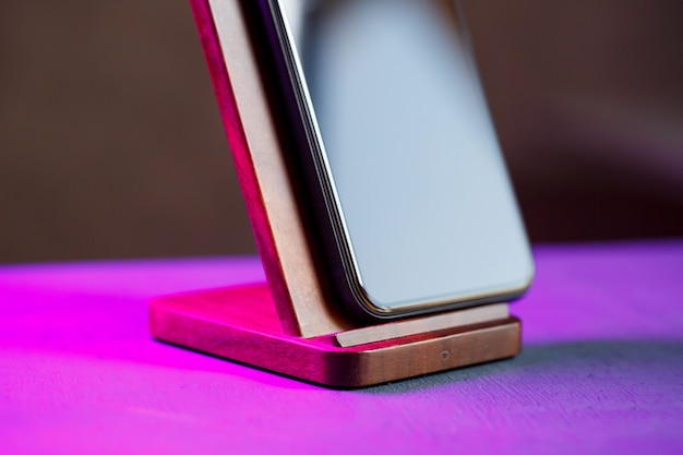 На деревянной подставке стоит черный телефон. беспроводная зарядка для телефона