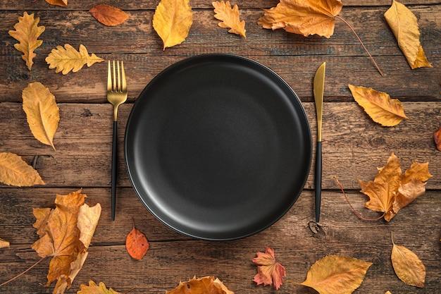 Черная тарелка и столовые приборы среди осенних листьев на деревянном фоне