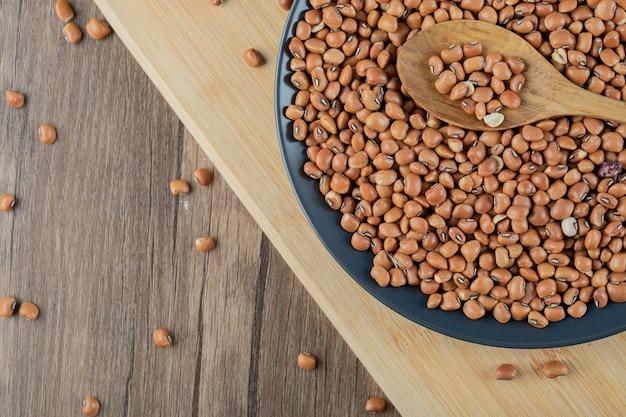 木のスプーンで乾燥した生の小豆でいっぱいの黒いプレート。