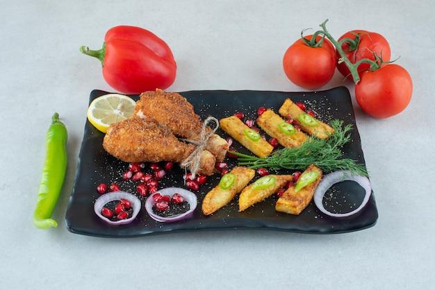 토마토와 후추와 프라이드 치킨 가득한 검은 접시.