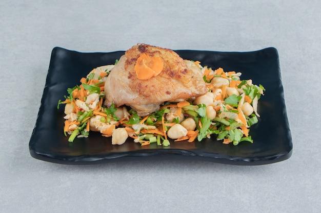 Черная тарелка куриного жареного мяса и овощного салата.