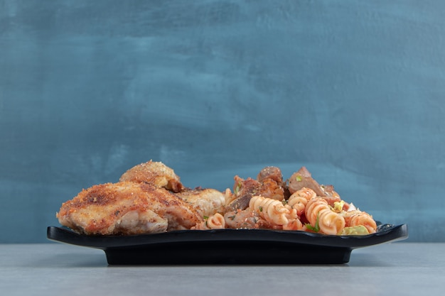 닭고기 튀김 고기와 야채 샐러드의 검은 접시.