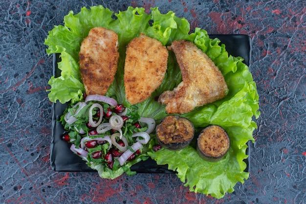야채와 닭고기의 검은 접시.