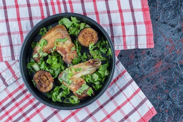 Черная тарелка куриного мяса с овощами.