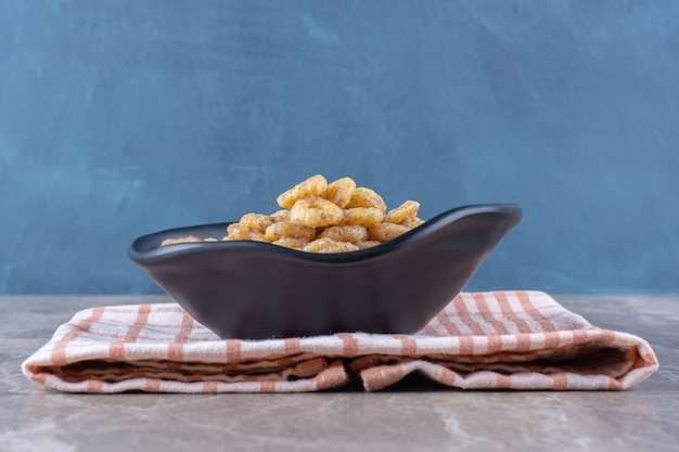 Черная тарелка здоровых зерновых колец на завтрак на скатерти.