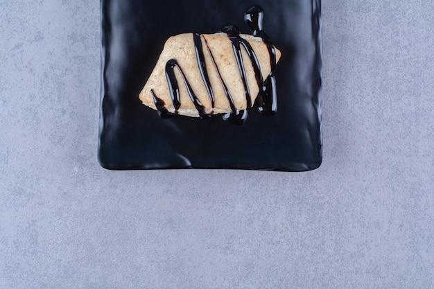 チョコレートシロップとクリームが入った甘いクッキーの黒いプレート。