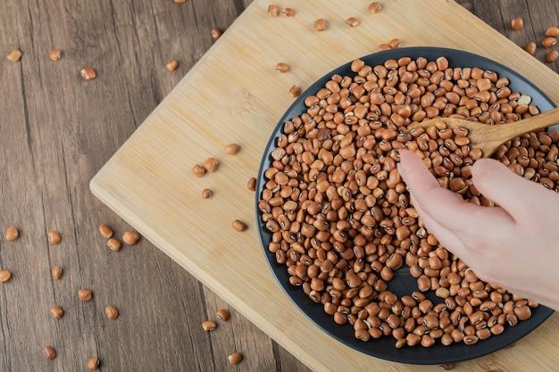 Черная тарелка с сырой коричневой фасолью на деревянном столе.