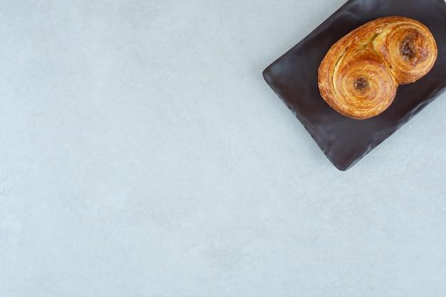 Черная тарелка со сладкой вкусной выпечкой на белом столе.